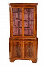 A George III style mahogany standing corner cabinet, the dentil moulded canted cornice above a conforming case fitted with a pair of astragal glazed doors, enclosing a velvet lined interior, the base with a pair of fielded ogee panel doors, raised on