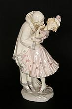 An early 20th Century faience figural lamp base, modelled as Pierrot and Pierrette, signed Podany, blue printed Vienna Faience Schauer factory mark. 43.5cm